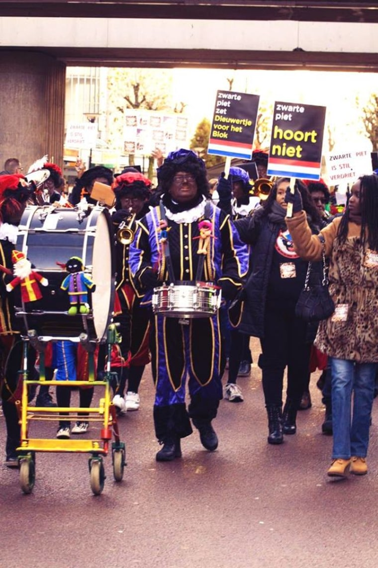 "Protestors held signs saying ""Zwarte Piet Should Not Be Here"" and repeated, "" Zwarte Piet is Racism"" as they walked behind a group of men donning blackface as Zwarte Piet."