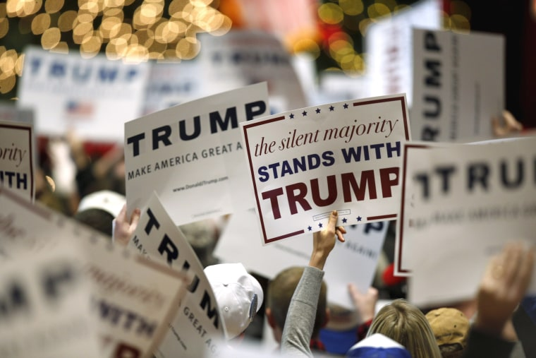 Image: Supporters hold signs for U.S. Republican presidential candidate Trump at a campaign event at the Veterans Memorial Building in Cedar Rapids