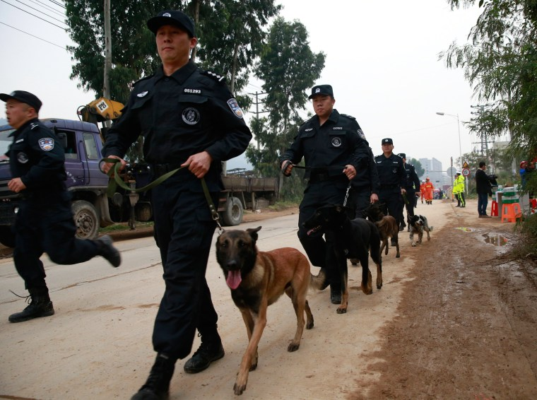 Image: Policemen with police dogs walk next to a site of a landslide which hit an industrial park in Shenzhen