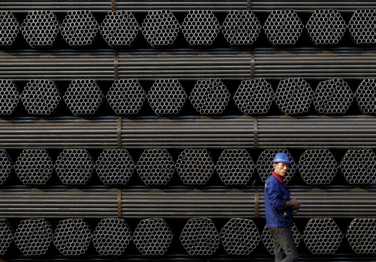 Image: File photo of a worker walking past a pile of steel pipe products at the yard of Youfa steel pipe plant in Tangshan in China's Hebei Province