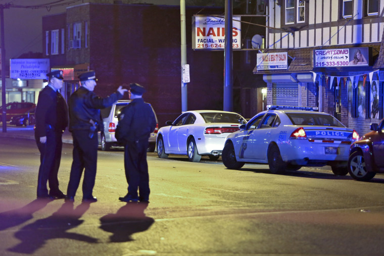 Investigators gather at the scene where a Philadelphia police officer shot and killed a man during a traffic stop in 2014.