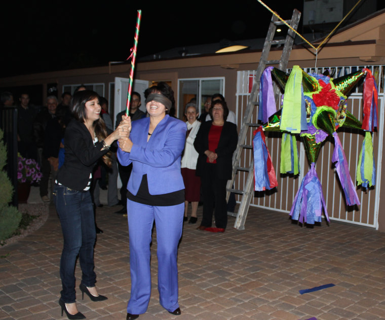 Griselda Nevarez (left) spinning her blindfolded mother right before she hits the piñata, part of the family's cherished Christmas traditions.
