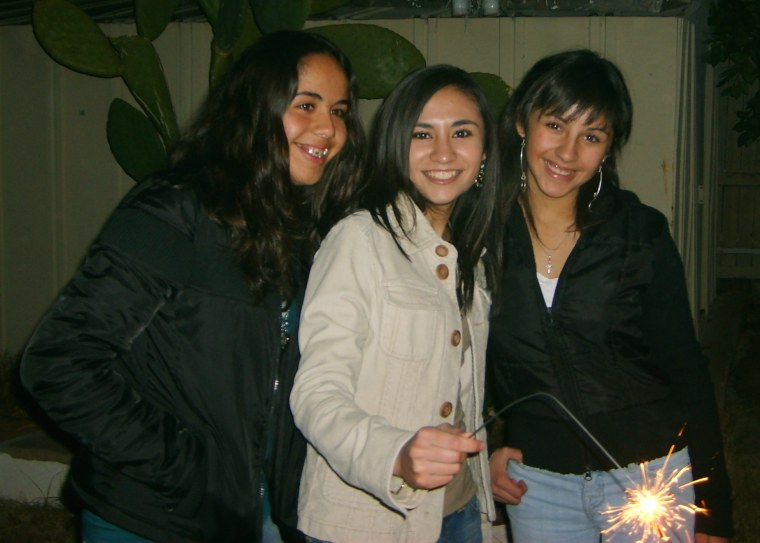Griselda Nevarez (center) is surrounded by her cousins as they light up sparklers for Christmas.