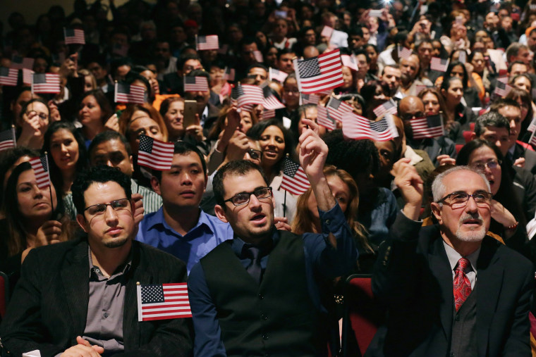 Image: New United States citizens wave flags and sing patriotic songs