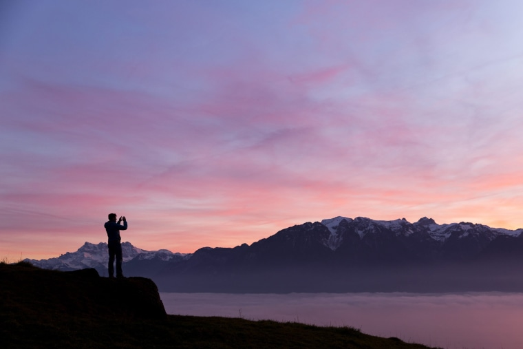 Image: A man takes a picture of the sea of fog that covers Geneva Lake