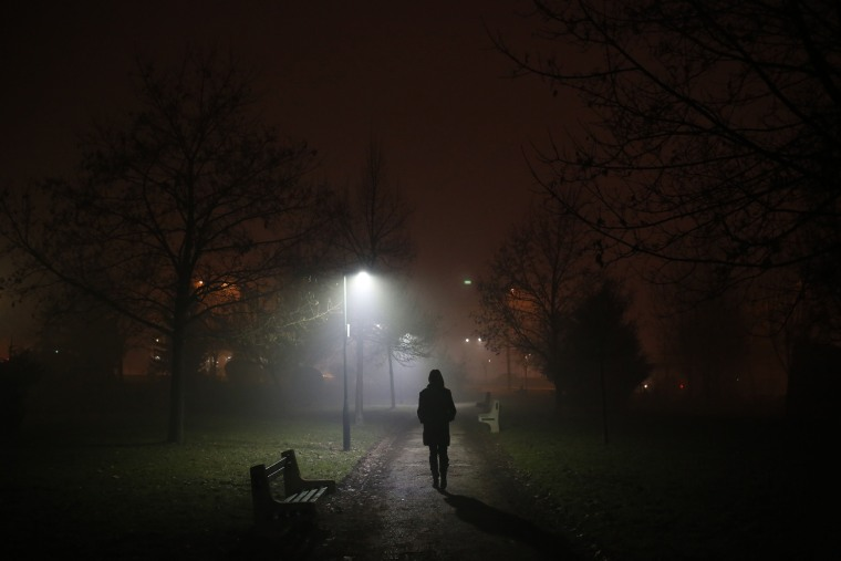 Image: A Bosnian woman walks on the street during fog in Sarajevo
