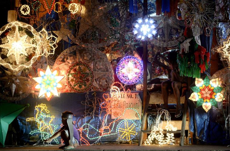 Image: Vendors wait for customers amongst Christmas lanterns