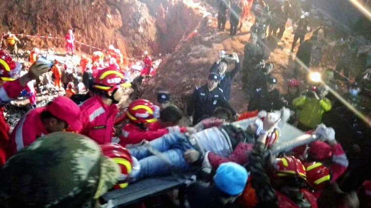 Image: Rescuers take out the first survivor of the landslide in Shenzhen