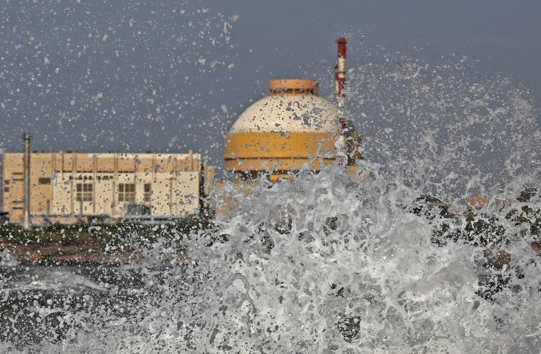 Image: File photo shows sea waves hitting the rocks as Kudankulam nuclear power project plant in the background