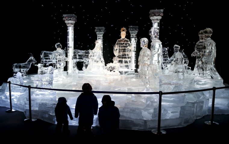 Image: Children stand in front of a nativity scene made entirely of ice, part of the ICE! event at Maryland's National Harbor just outside of Washington