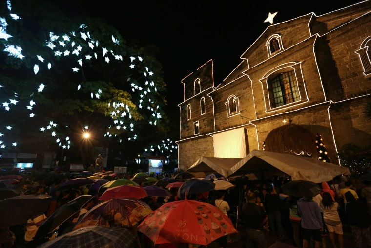 Image: Filipino Catholics attend the traditional Misa de Gallo (Dawn Mass) during a downpour