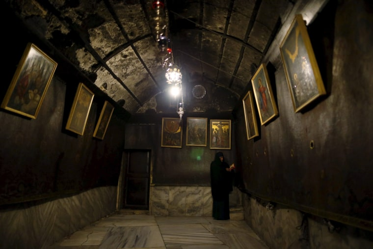 Image: A worshiper prays inside the cave, where Virgin Mary is believed to have given birth to Jesus under the Church of Nativity, ahead of Christmas in Bethlehem