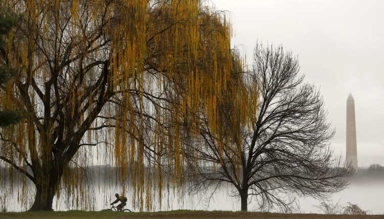 Image: A cyclist makes his way along the foggy Potomac in Washington