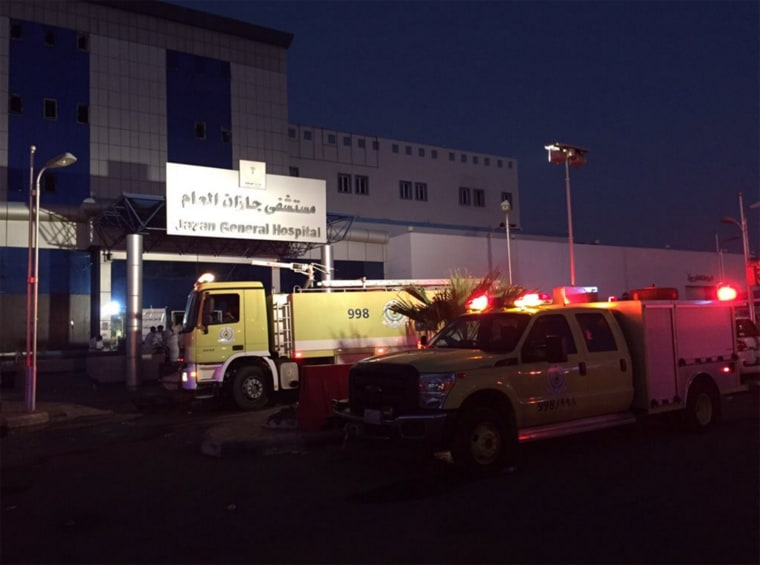 Officials at the scene of a hospital fire Thursday, Dec. 24, in Jazan, Saudi Arabia. At least 25 people were reportedly killed and over 100 others were injured.