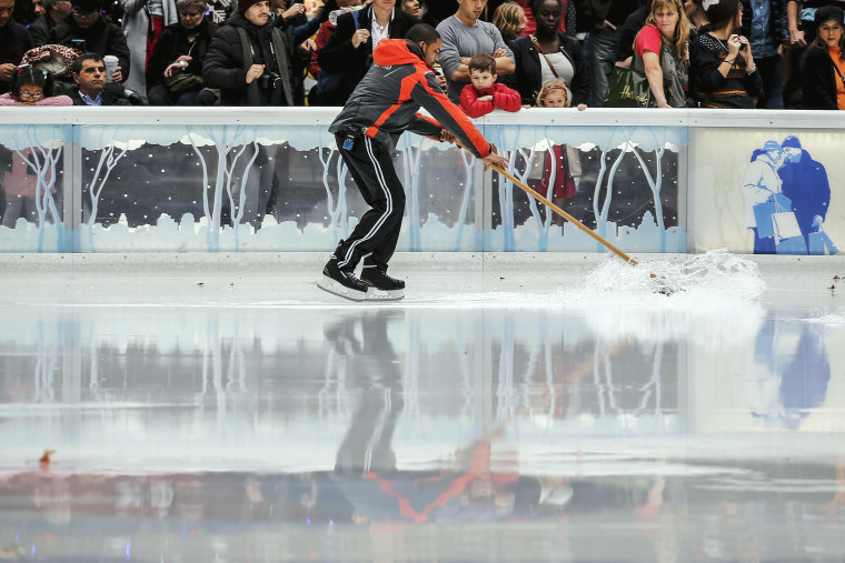 Image: A worker pushes water off the surface of the skating rink in Bryant Park during unseasonably warm weather on Christmas Eve in the Manhattan borough of New York