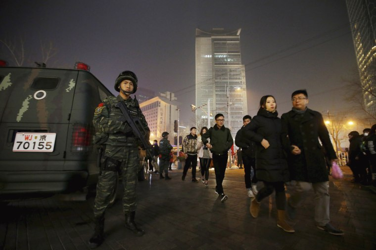 Image: An armed policeman from the Snow Leopard Commando Unit stands guard at the Sanlitun area on Christmas Eve in Beijing