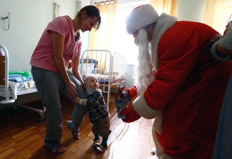Image: A man dressed as Father Frost, equivalent of Santa Claus, gives a present to a boy on the eve of Christmas in a burn unit of a hospital in Minsk
