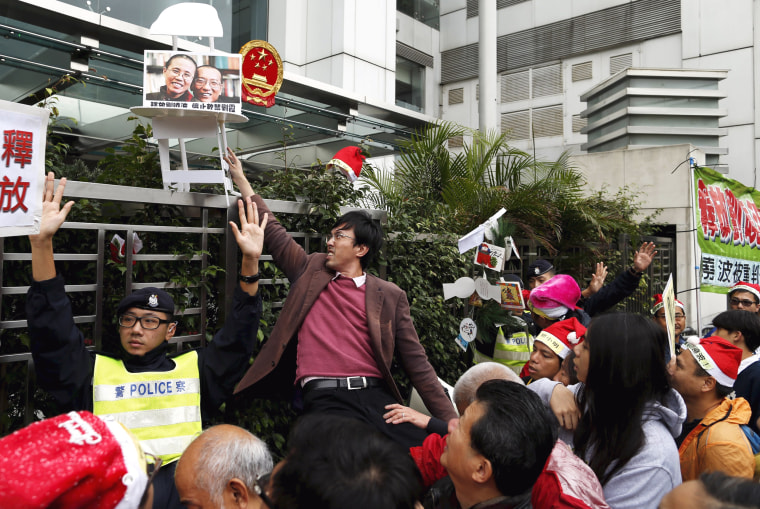 Image: A pro-democracy demonstrator holds up prop with a photo of Liu and his wife Liu Xia