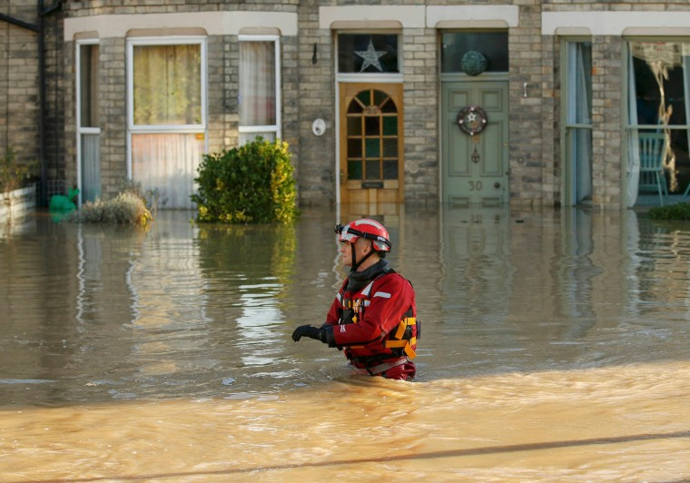 Image: A member of the emergency services navigates a flooded street in York, northern England