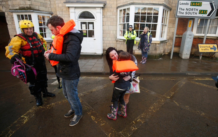 Image: Members of the emergency services rescue a group of people from a flooded street in Tadcaster, northern England