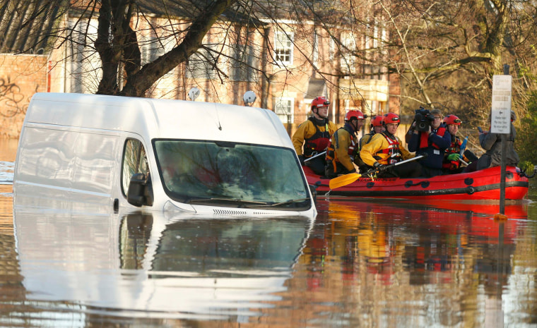 Image: Emergency services navigate a flooded street in York, northern England