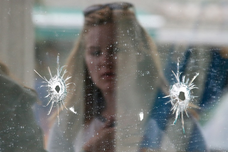 A woman looks at the bullet holes on the window of IV Deli Mark where a mass shooting took place near the University of California, Santa Barbara campus.