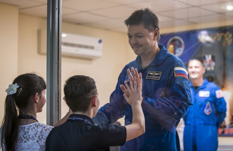 Image: The International Space Station crew member Kononenko of Russia interacts with his children as he stands behind a glass wall at a news conference at the Baikonur cosmodrome in Baikonur