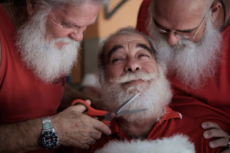 Image: A graduate of the Brazil's School of Santa Claus gets his beard trimmed by students in Rio de Janeiro, Brazil