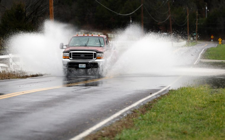 Image: The driver of a pickup truck crosses a flooded section of road