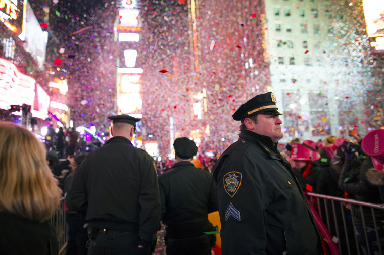 New York City police officers stand among the falling confetti just after midnight in Times Square during New Year's Eve festivities on Jan. 1, 2015.