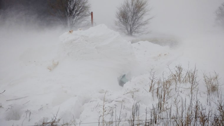 Jimmy and Betty Anderson were stuck in this 12-foot snowdrift in New Mexico for 20 hours. The windshield of their vehicle is visible at center right.