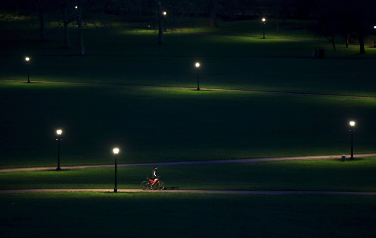 Image: A cyclist rides through Primrose Hill in the early evening in London