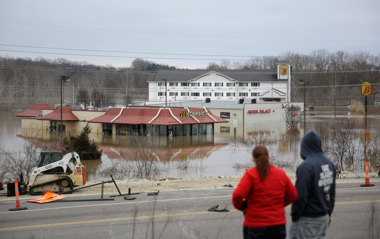 Image: People stand on a hill to get a better look at floodwater