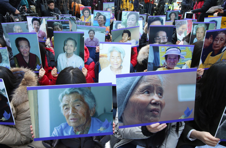 Image: South Korean supporters of former so-called comfort women, hold up pictures of deceased former comfort women