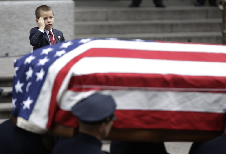 Image: Ryan Lemm, 4, son of Joseph Lemm, salutes as his father's casket is carried out of St. Patrick's Cathedral