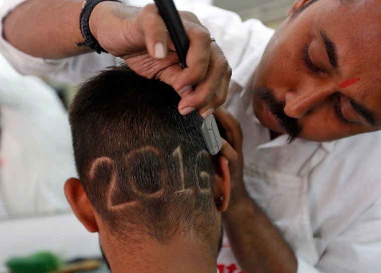 Image: A man gets a haircut depicting 2016 to welcome the New Year at a barbershop in Ahmedabad