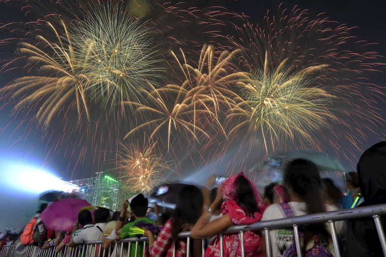 Image: Revelers watch as fireworks explode during New Year celebrations outside the Philippine Arena in Bocaue town, Bulacan province, north of Manila