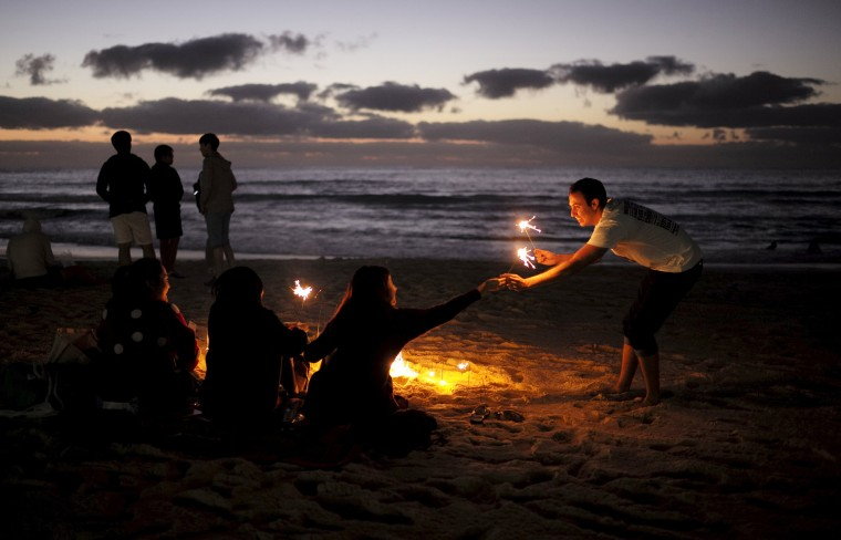 Image: Partygoers await the first sunrise of the new year on Australia's Bondi Beach in Sydney