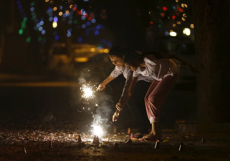 Image: Residents light firecrackers on the street during the New Year celebrations in Mumbai