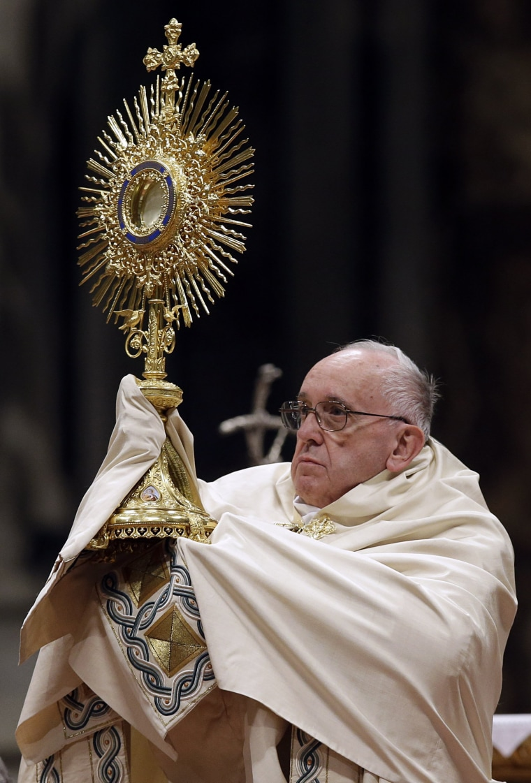 Image: Pope Francis holds a monstrance as he celebrates a new year's eve vespers Mass