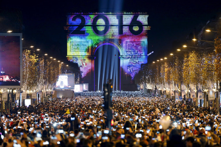 Image: Revellers gather near the Arc de Triomphe on the Champs Elysees Avenue in Paris during New Year celebrations