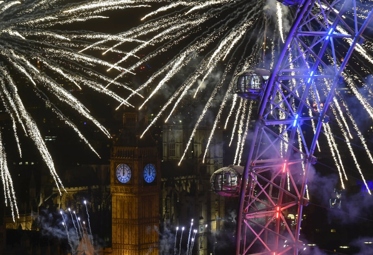 Image: Fireworks explode around the London Eye wheel, the Big Ben clock tower and the Houses of Parliament to mark the beginning of the New Year in London