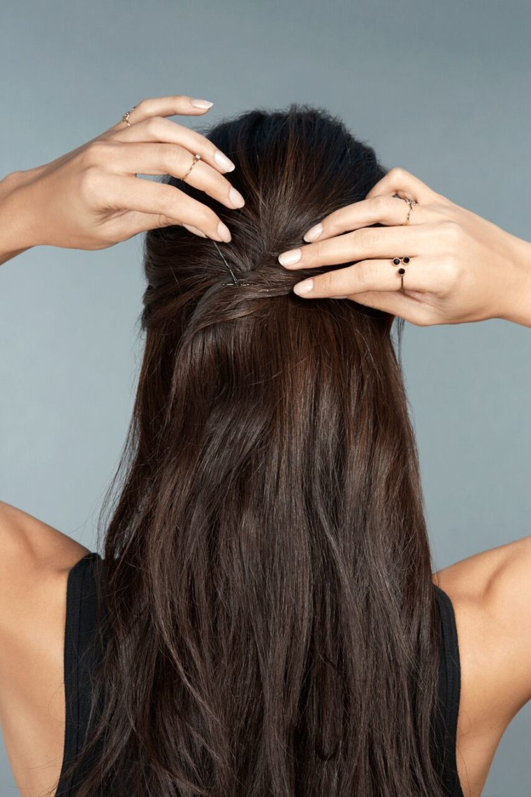 2)	Divide the hair into three sections, leaving the middle as the thickest.