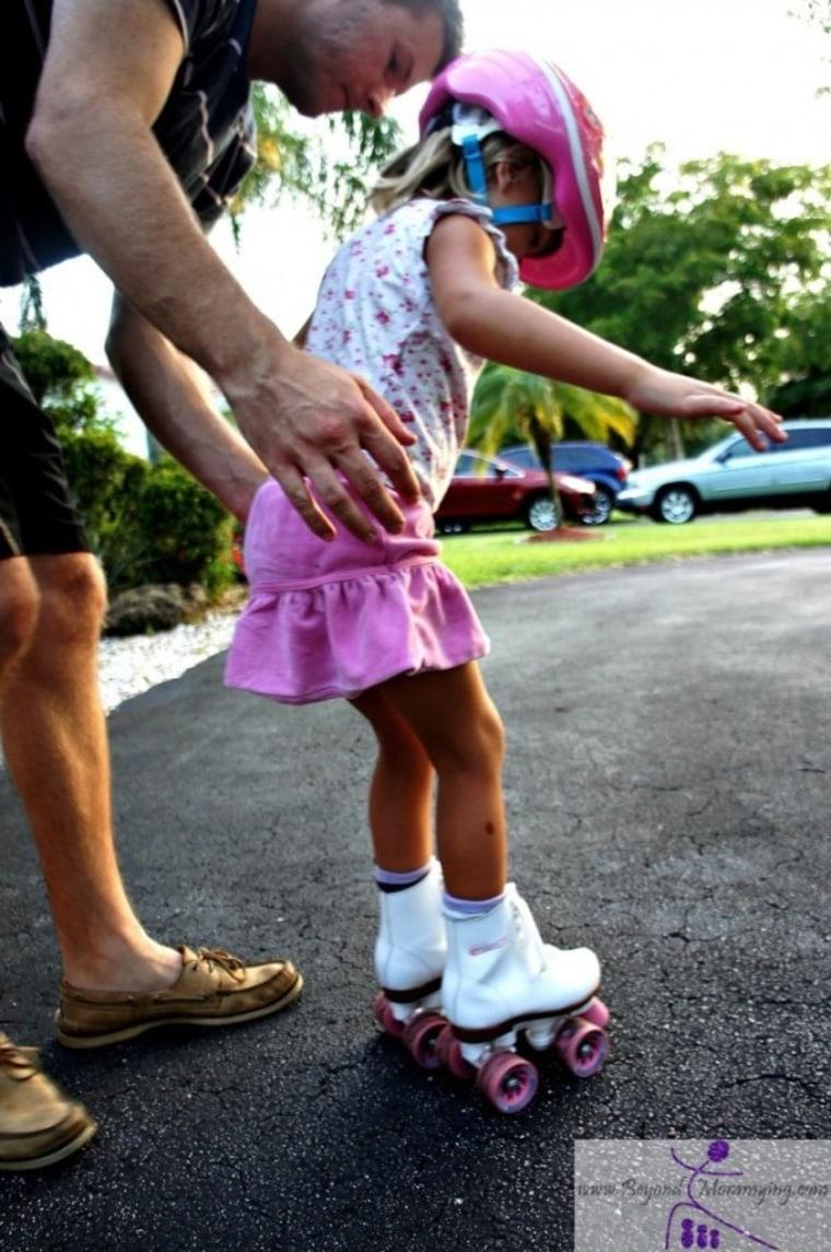 Dad helping his daughter to rollerskate