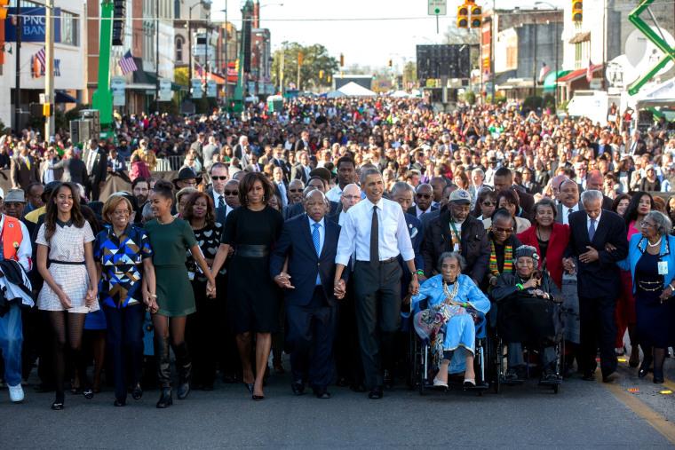 Barack Obama and Michelle Obama walk across the Edmund Pettus Bridge