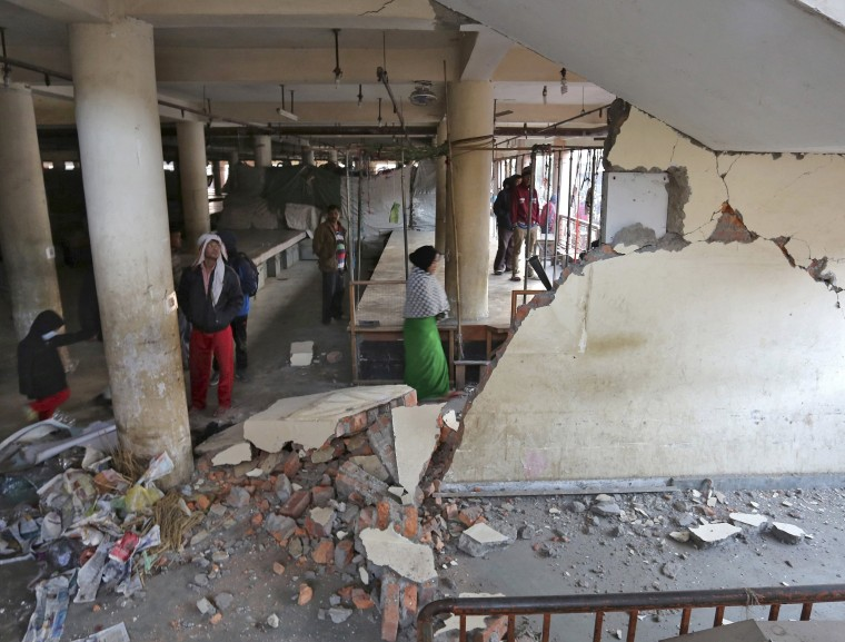 Image: People look at a damaged building at a market place