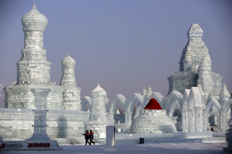 Image: People look around ice sculptures ahead of the Harbin International Ice and Snow Festival in the northern city of Harbin