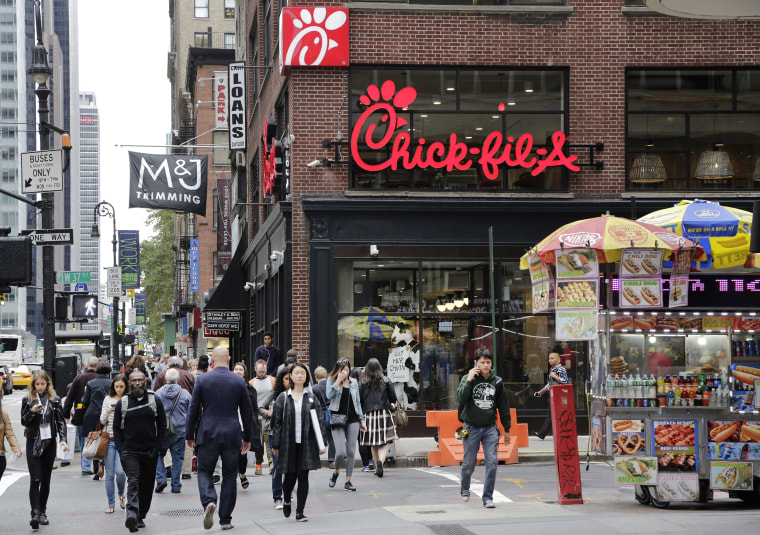 Image: People walk past a Chick-fil-A restaurant in New York City