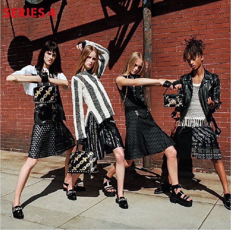 Jaden Smith poses alongside three female models, wearing a leather motorcycle-style jacket over a fringe top and a pleated skirt.