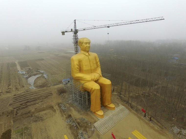 Image: A crane is seen next to a giant statue of Chinese late chairman Mao Zedong under construction near crop fields in a village of Tongxu county, China